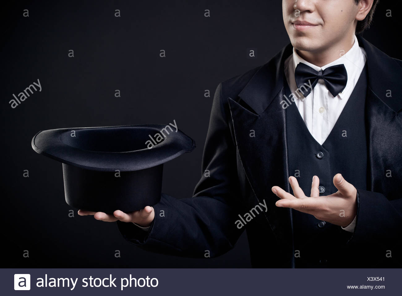 magician showing tricks with top hat isolated - Stock Image