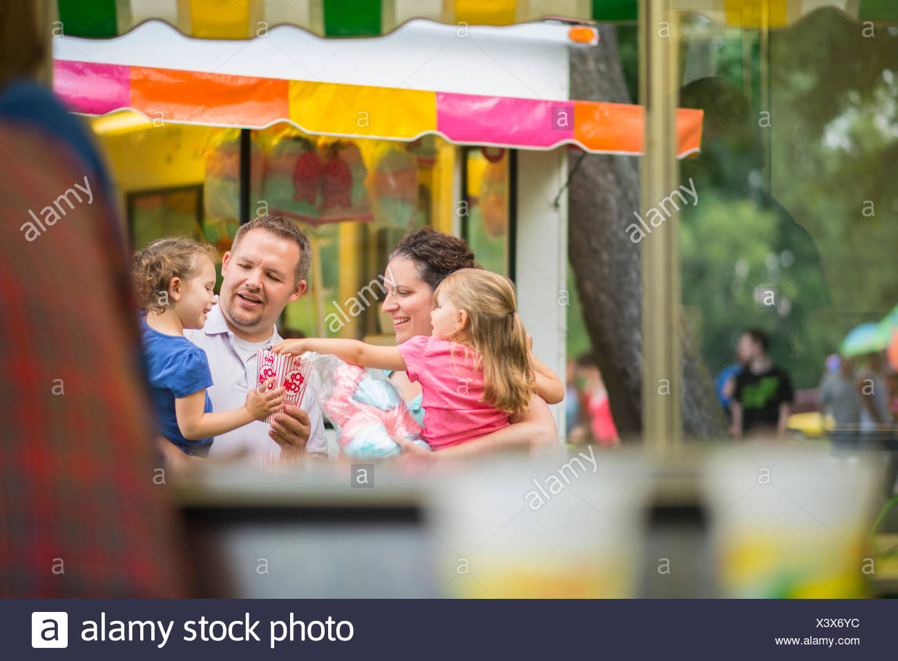 Mid adult couple and two young daughters eating popcorn at funfair - Stock Image