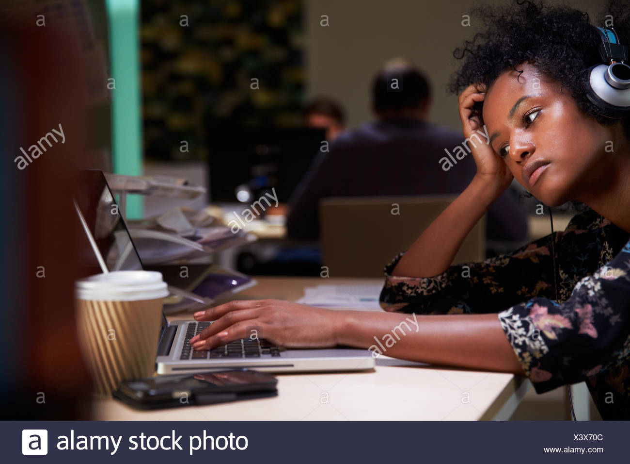 Female Office Worker With Coffee At Desk Working Late - Stock Image