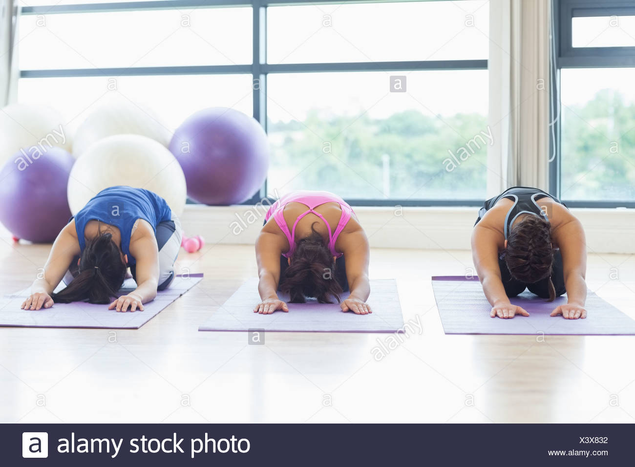 Fit women bending over on exercise mats in fitness studio - Stock Image