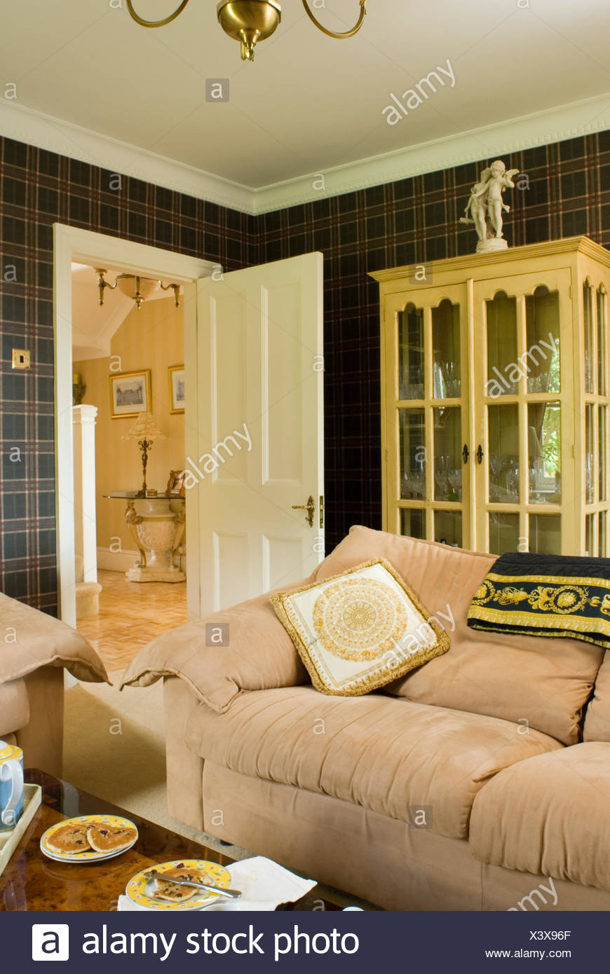 Cream velour sofa in front of glass-fronted cupboard in country living room - Stock Image