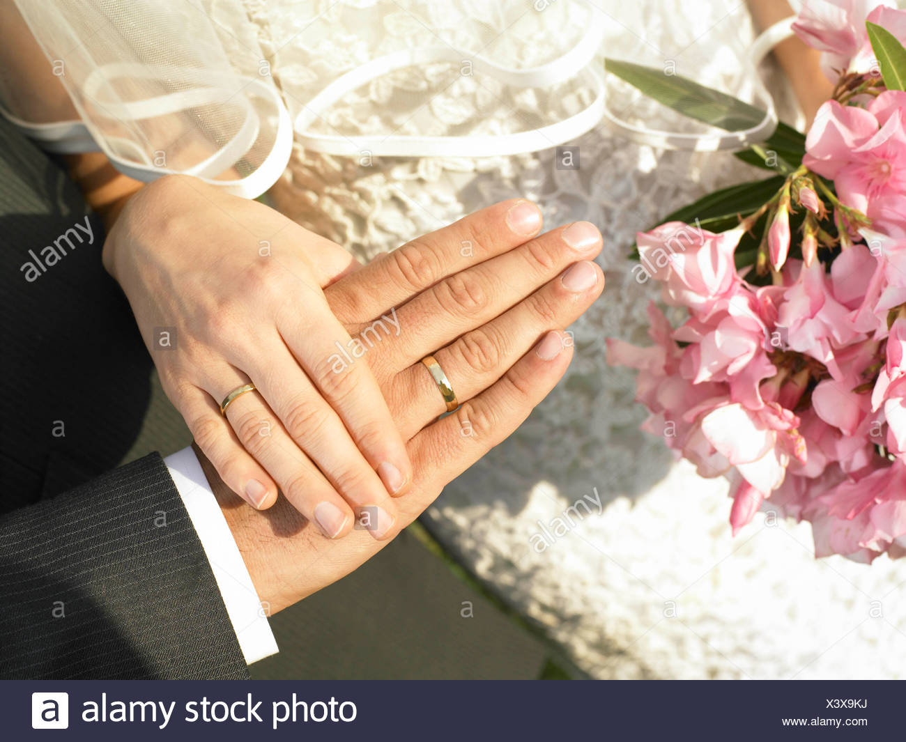 Bride and groom hands with wedding rings - Stock Photo