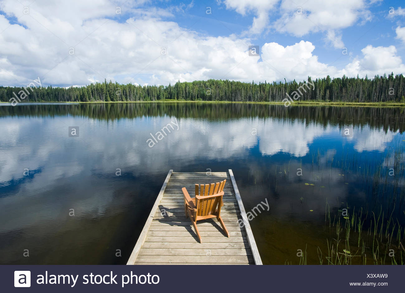 chair on dock, Two Mile Lake , Duck Mountain Provincial Park, Manitoba, Canada - Stock Image