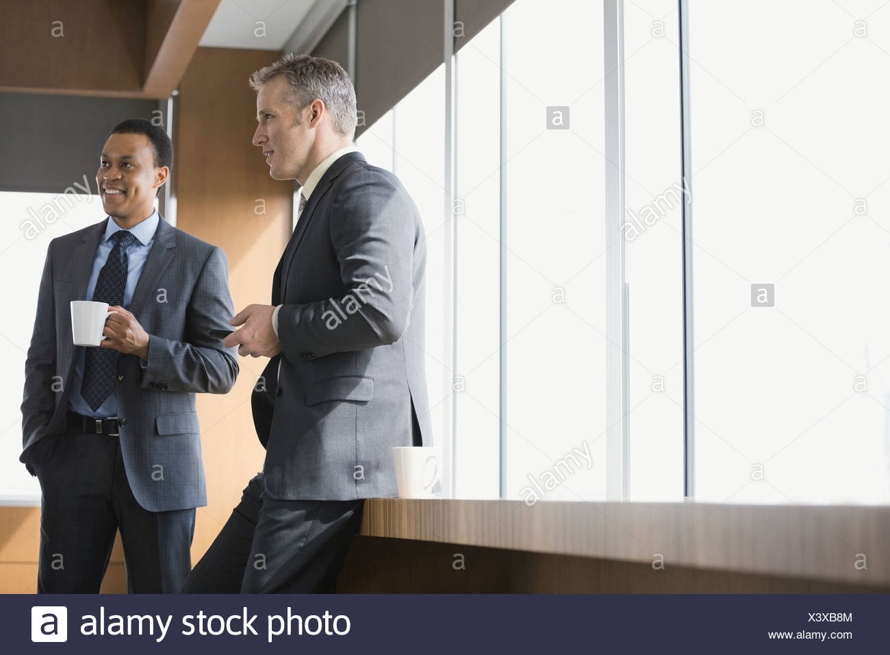 Businessmen talking in conference room - Stock Image