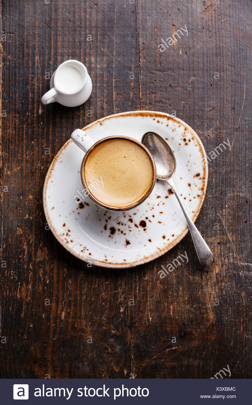 Espresso cup with milk on wooden background - Stock Image