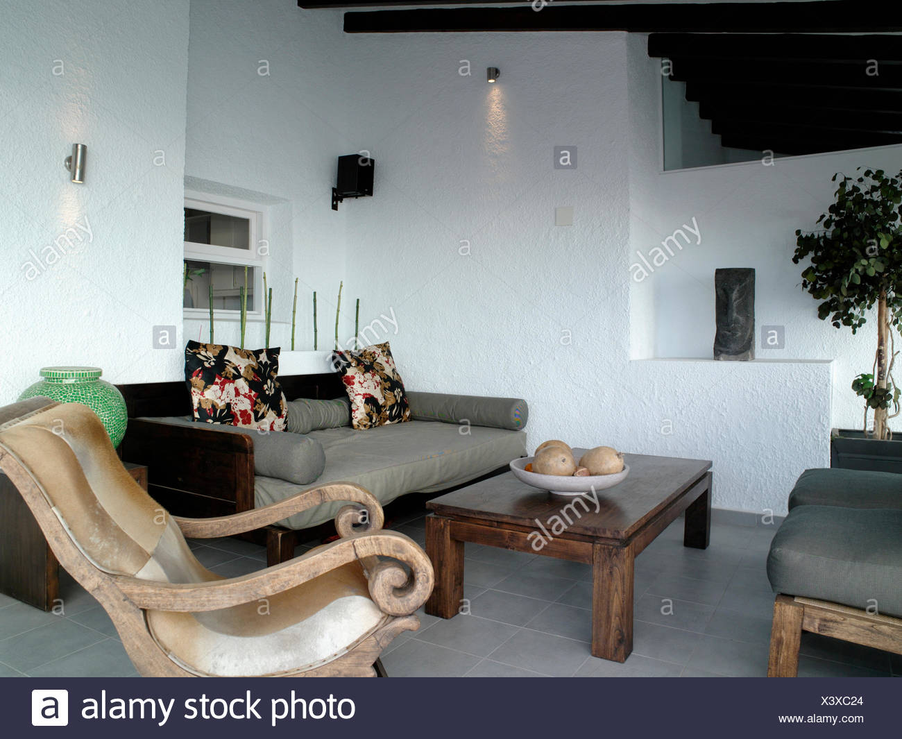 Dark wood coffee-table and gray sofa in modern white coastal ...