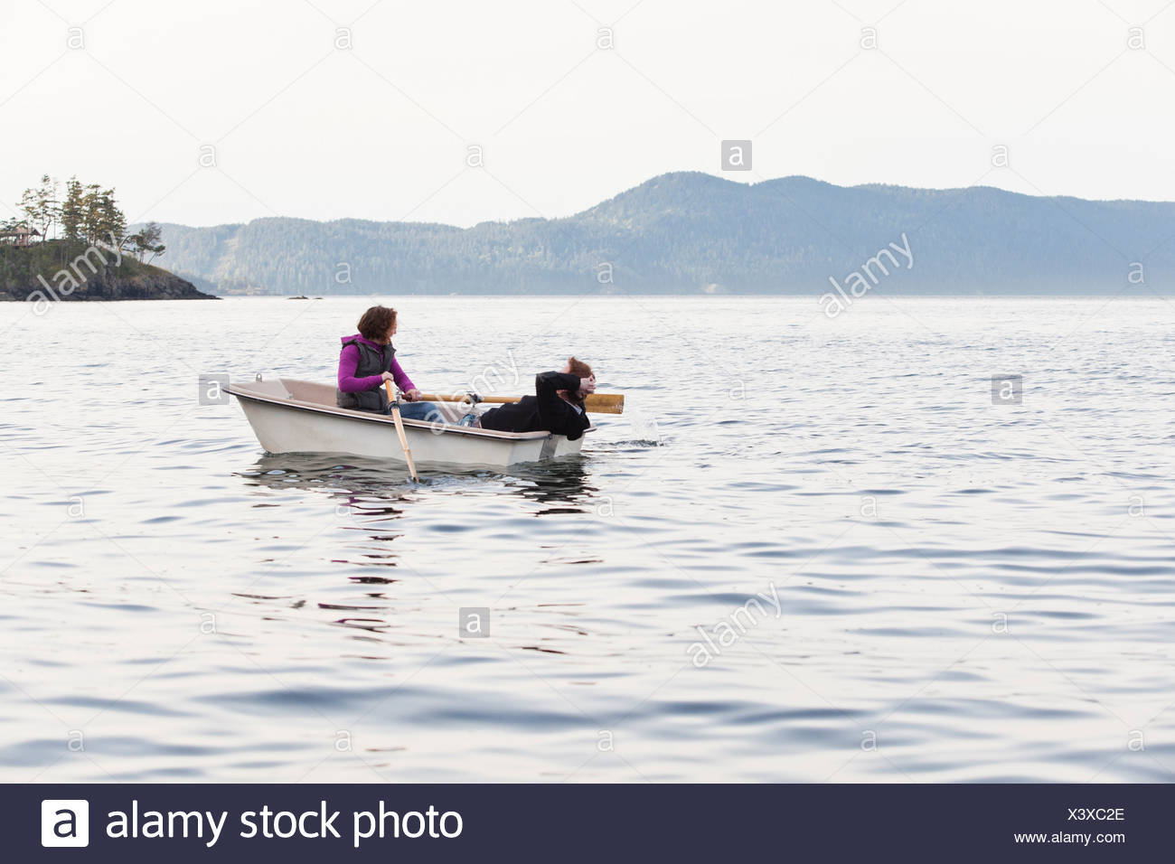 A young couple row out into the Puget Sound from Orcas Island in a small row boat. - Stock Image