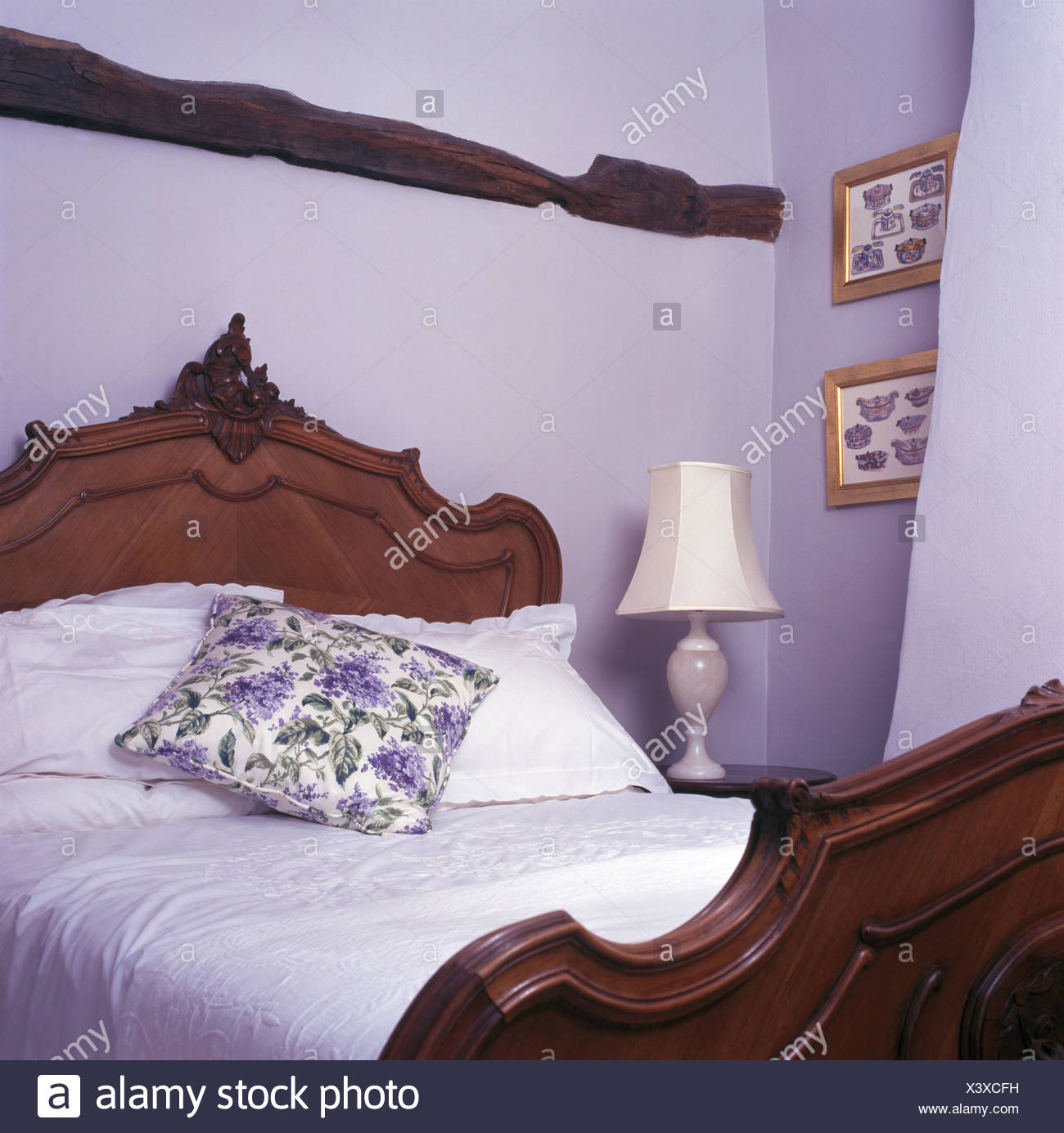 Cottage bedroom with lamp beside carved wooden bed with a ...