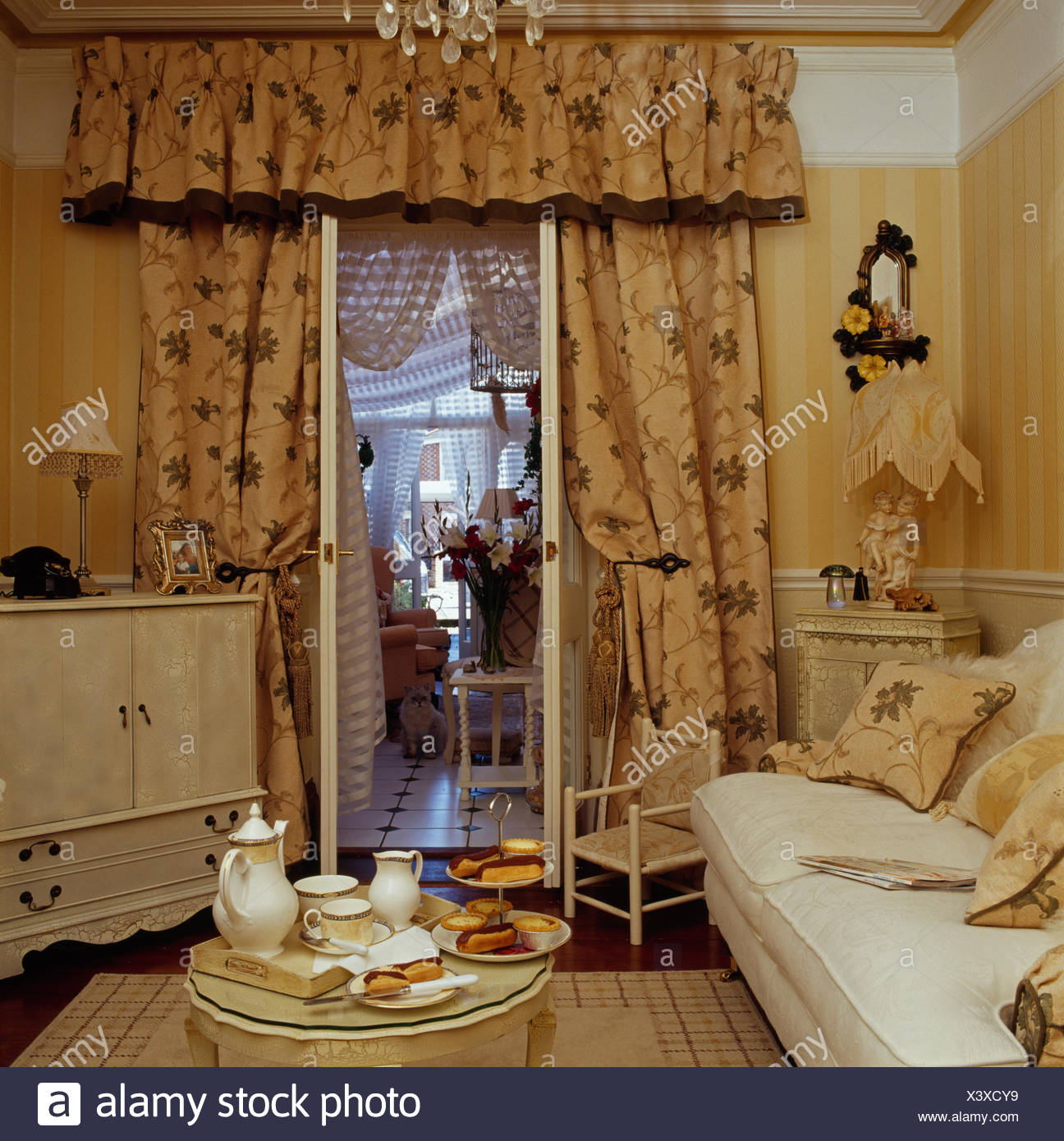 Tea Set On Tray In Small Living Room With Concealed Television And Patterned Curtains At Open French Windows To Conservatory Stock Photo Alamy