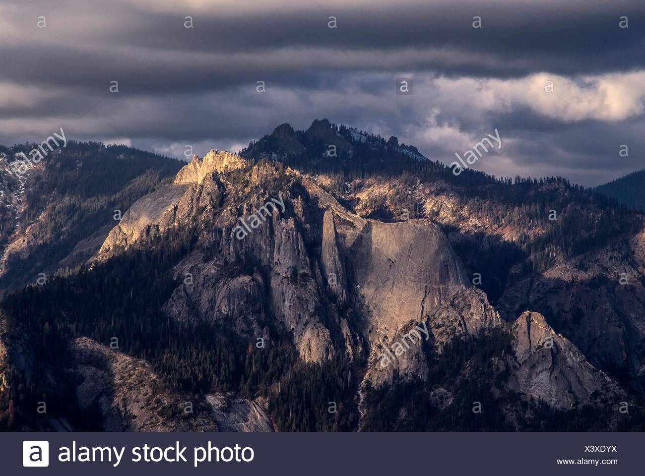 Light from the setting sun shines on Castle Rocks at Sequoia National Park, California. - Stock Image