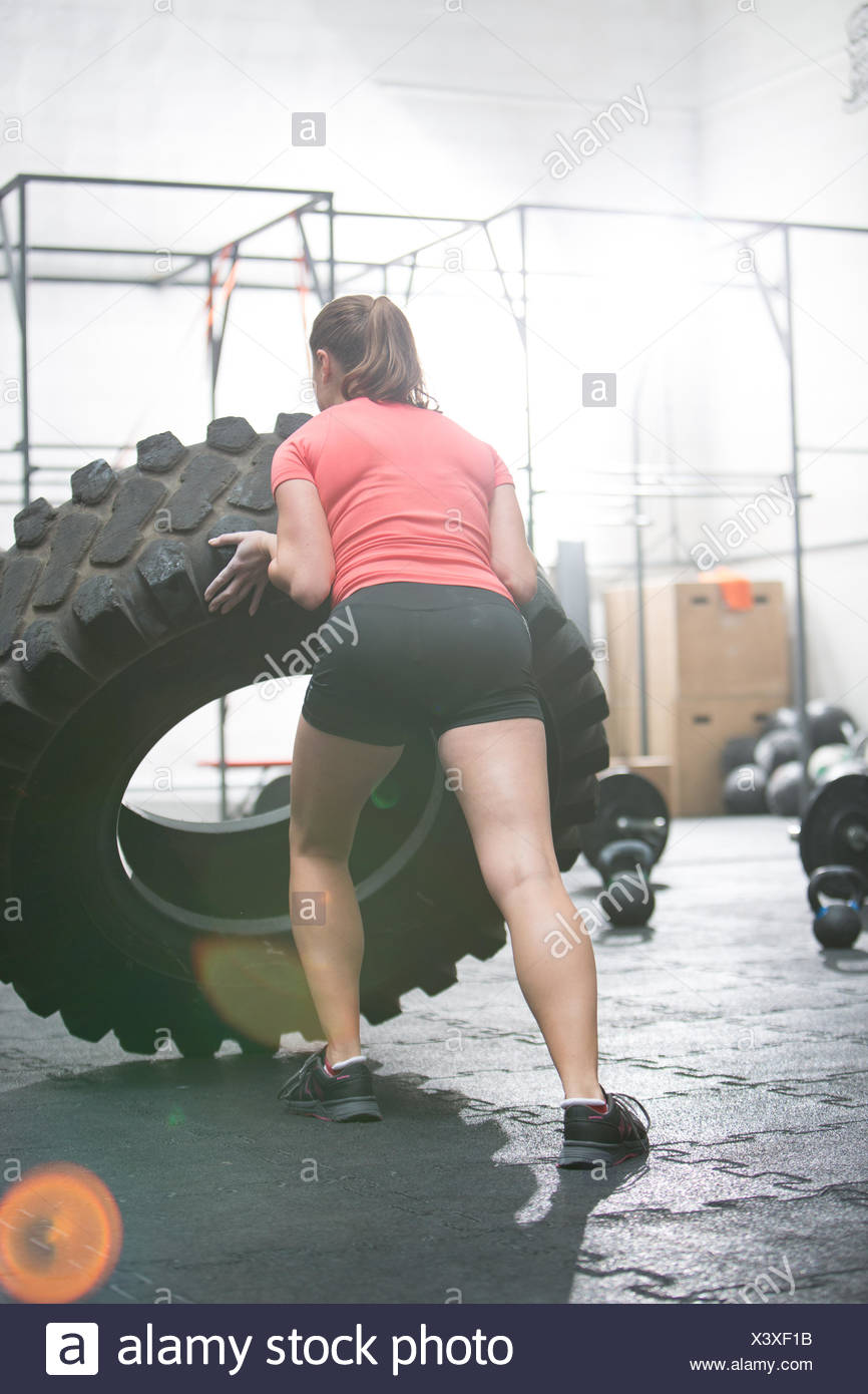 Rear view of woman flipping tire in gym - Stock Image