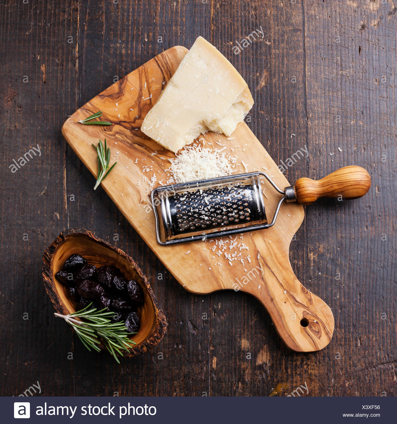 Parmesan cheese and sun-dried olives on olive wood cutting board - Stock Image