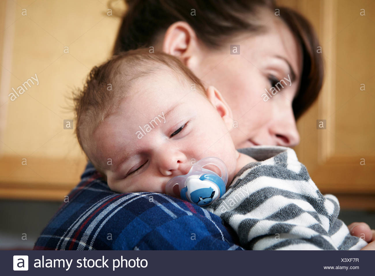 Mother holding sleeping baby boy - Stock Image