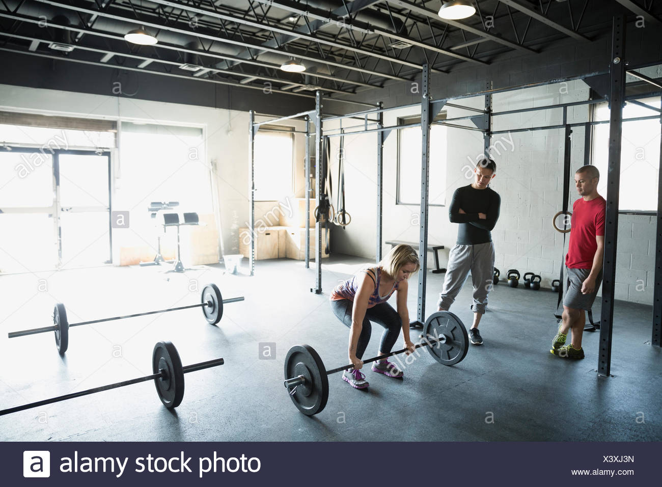 Woman squatting with barbell at gym - Stock Image