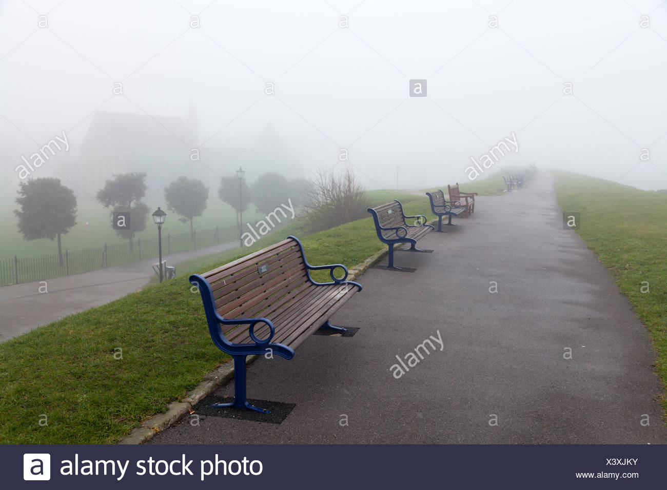 Empty unoccupied benches in fog in a line - Stock Image
