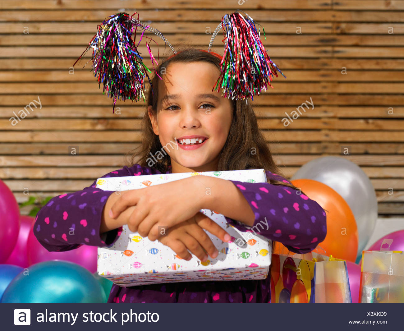 Girl (8-10) holding birthday present - Stock Image