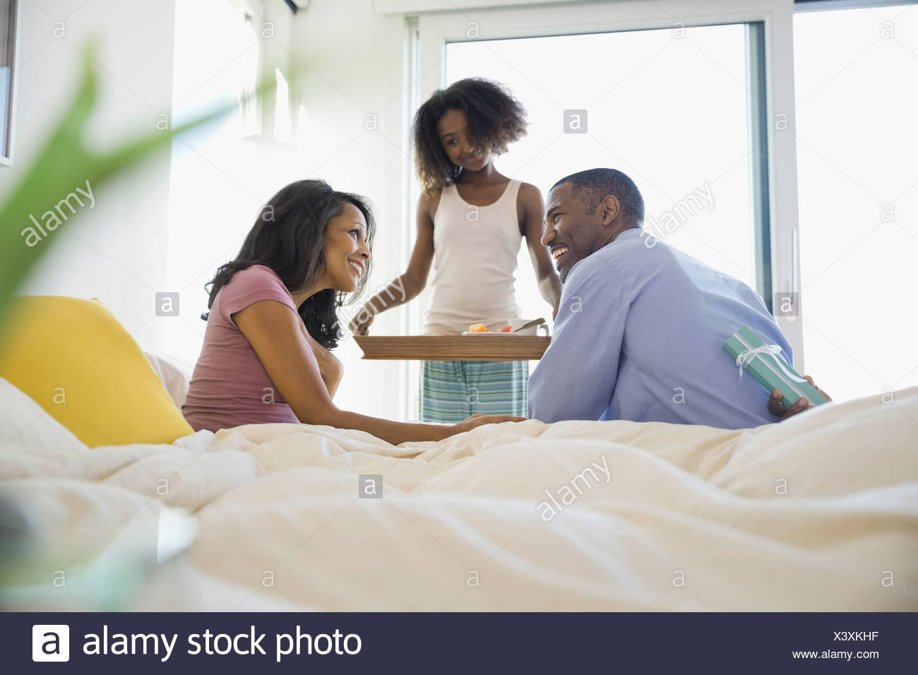 Family surprising woman with birthday breakfast in bed - Stock Image