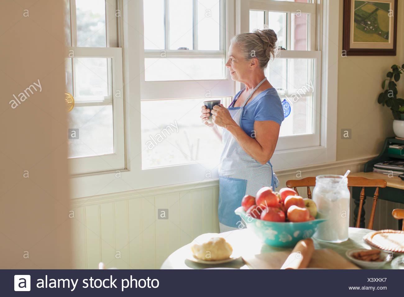 Woman gazing out window while enjoying coffee. - Stock Image