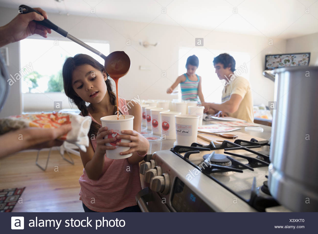 Mother and daughter cooking soup, pouring into container in kitchen - Stock Image