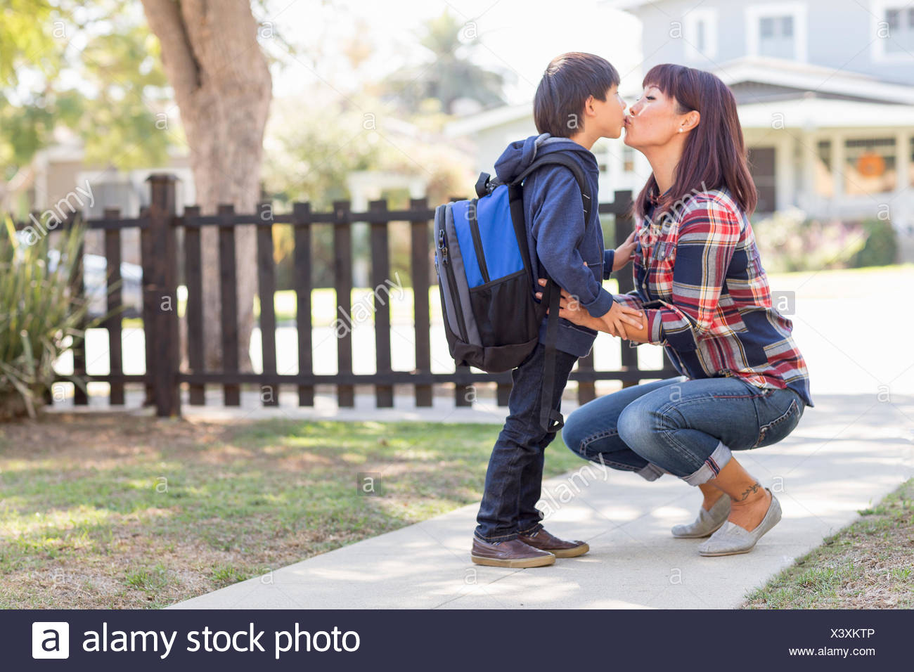 Mother kissing school boy son with backpack goodbye in front yard - Stock Image