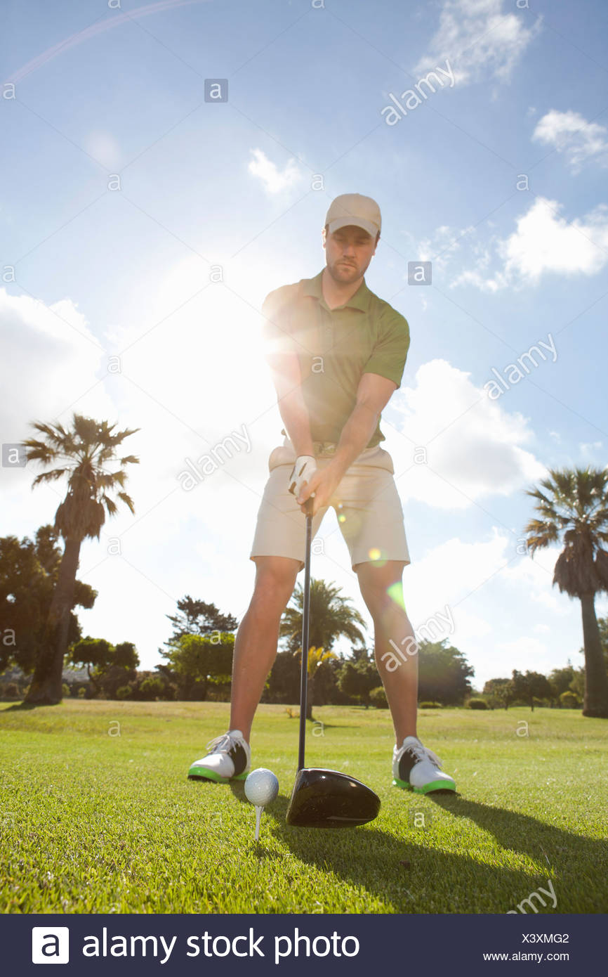 Young male golfer teeing off on the green - Stock Image