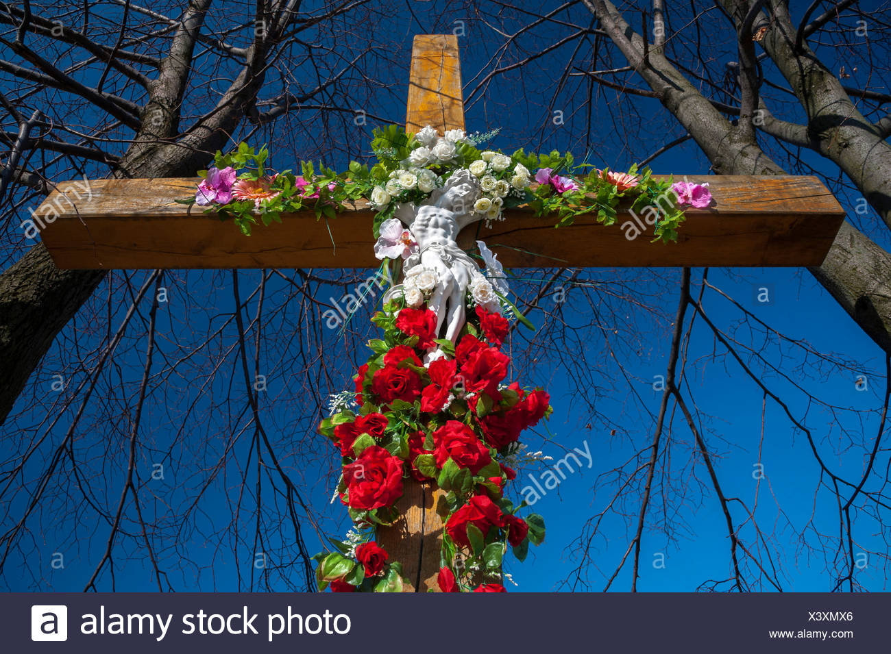 Crucifix decorated with flowers, in Tarnow, Lesser Poland, Poland, Europe - Stock Image