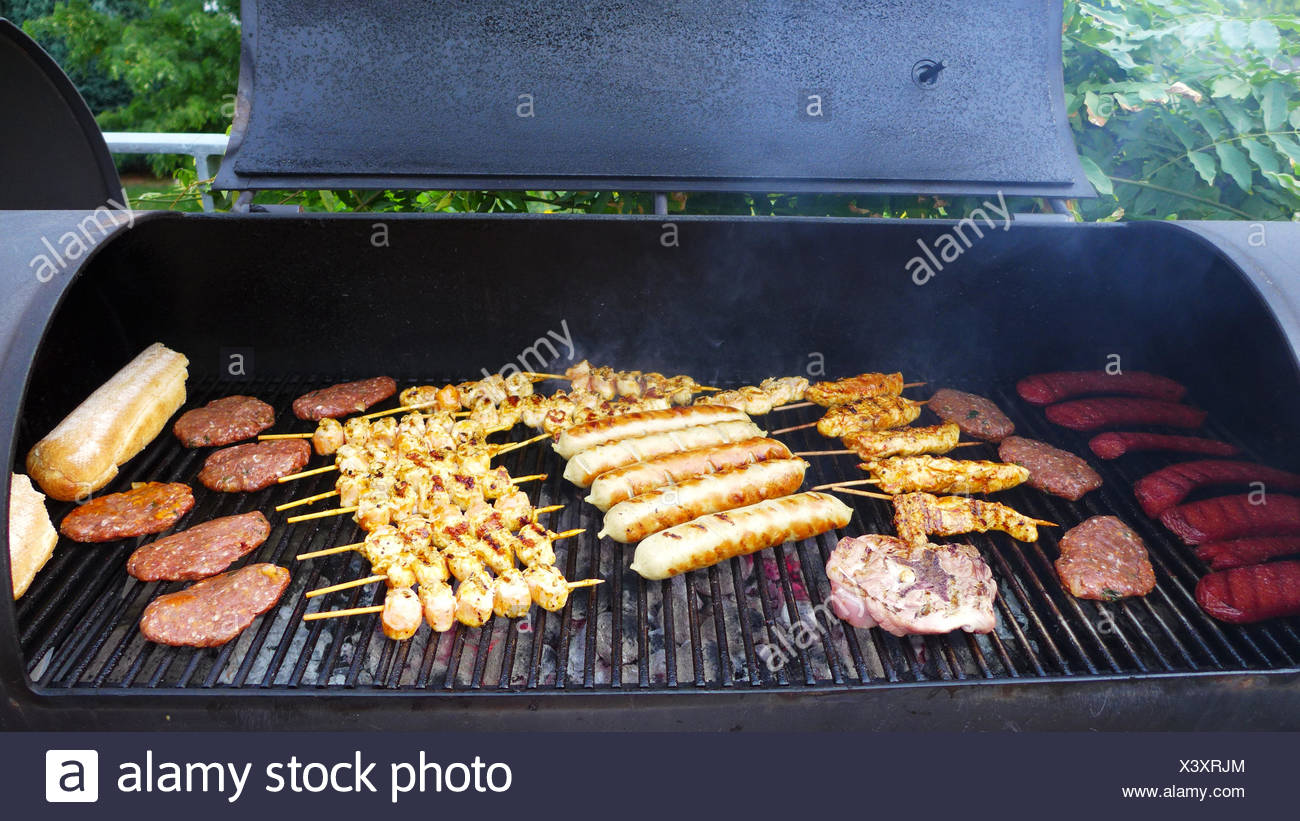 grill meat in a Barbecue-Smoker - Stock Image