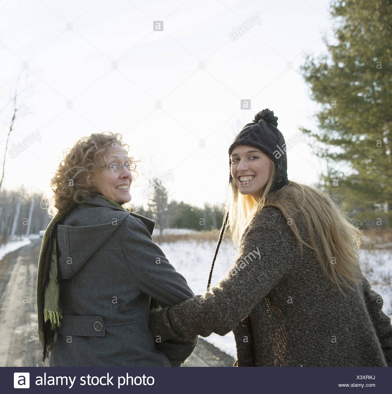 A mother and daughter arm in arm walking along a path and looking over their shoulders - Stock Image