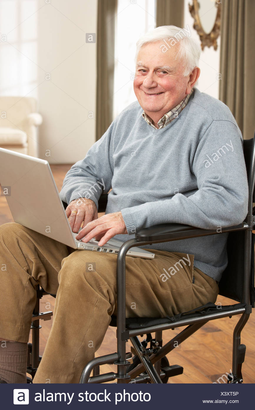 Disabled Senior Man Sitting In Wheelchair Using Laptop - Stock Image