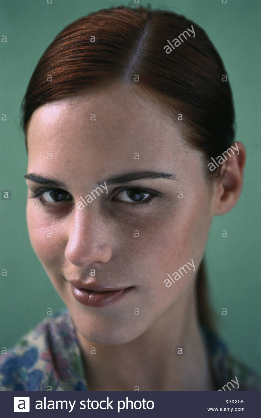Young woman smirking at camera, portrait - Stock Image