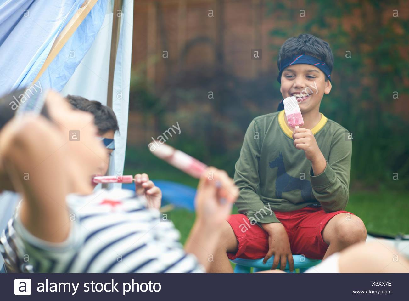 Girl and two brothers eating ice lollies in garden Stock Photo