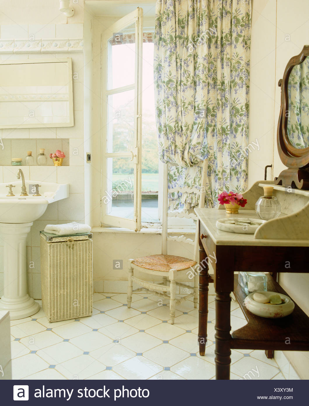 Marble Topped Washstand And White Tiled Floor In French Country Bathroom With Blue Floral Curtains And Pedestal Washbasin Stock Photo Alamy
