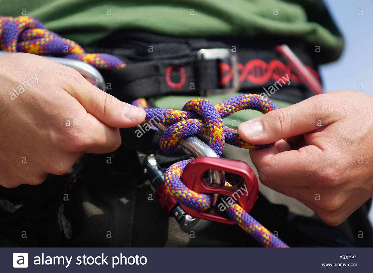 Man undoing hitch from gripping climbing rope, close-up - Stock Image