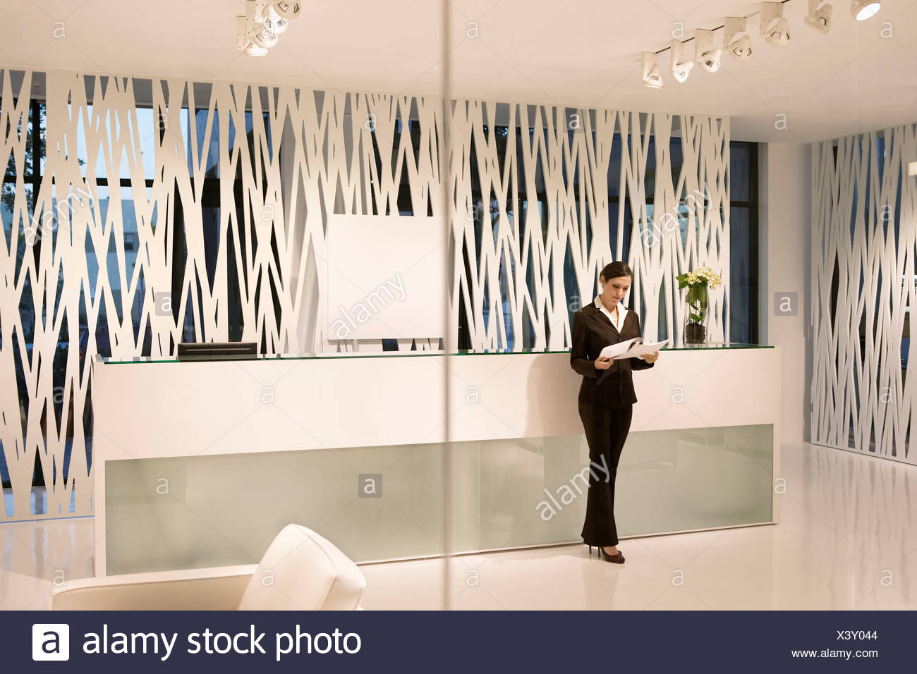 Businesswoman Reviewing Paperwork In Modern Office Lobby Stock Photo