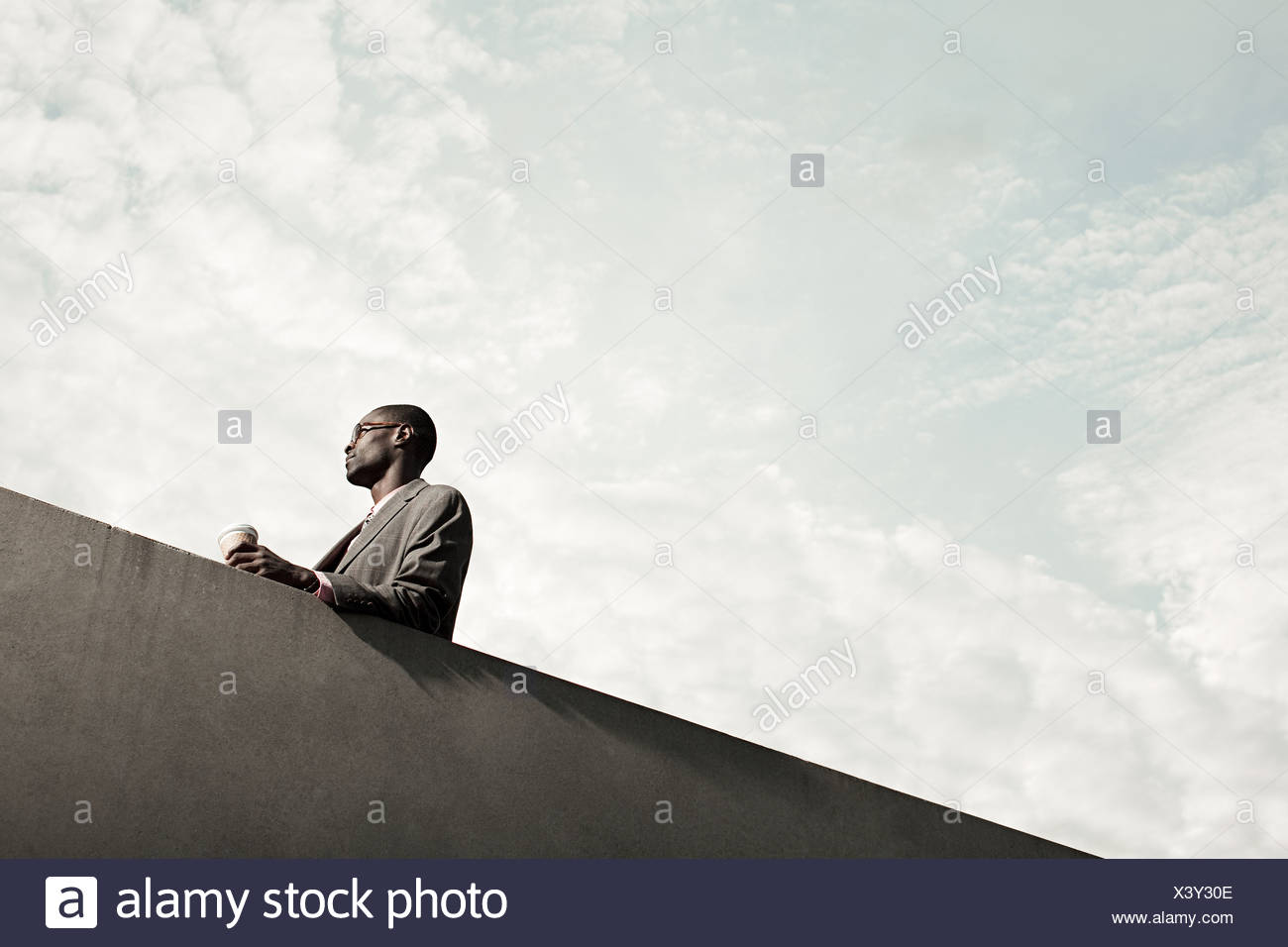 Businesswoman by wall with disposable cup, low angle - Stock Image