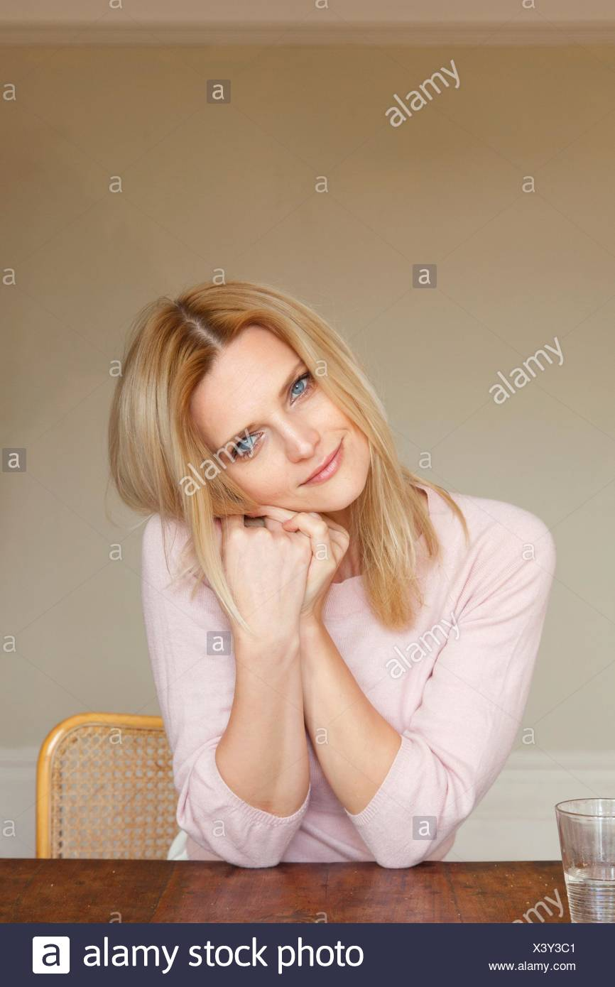 Portrait of beautiful mid adult woman with hands on cheek - Stock Image