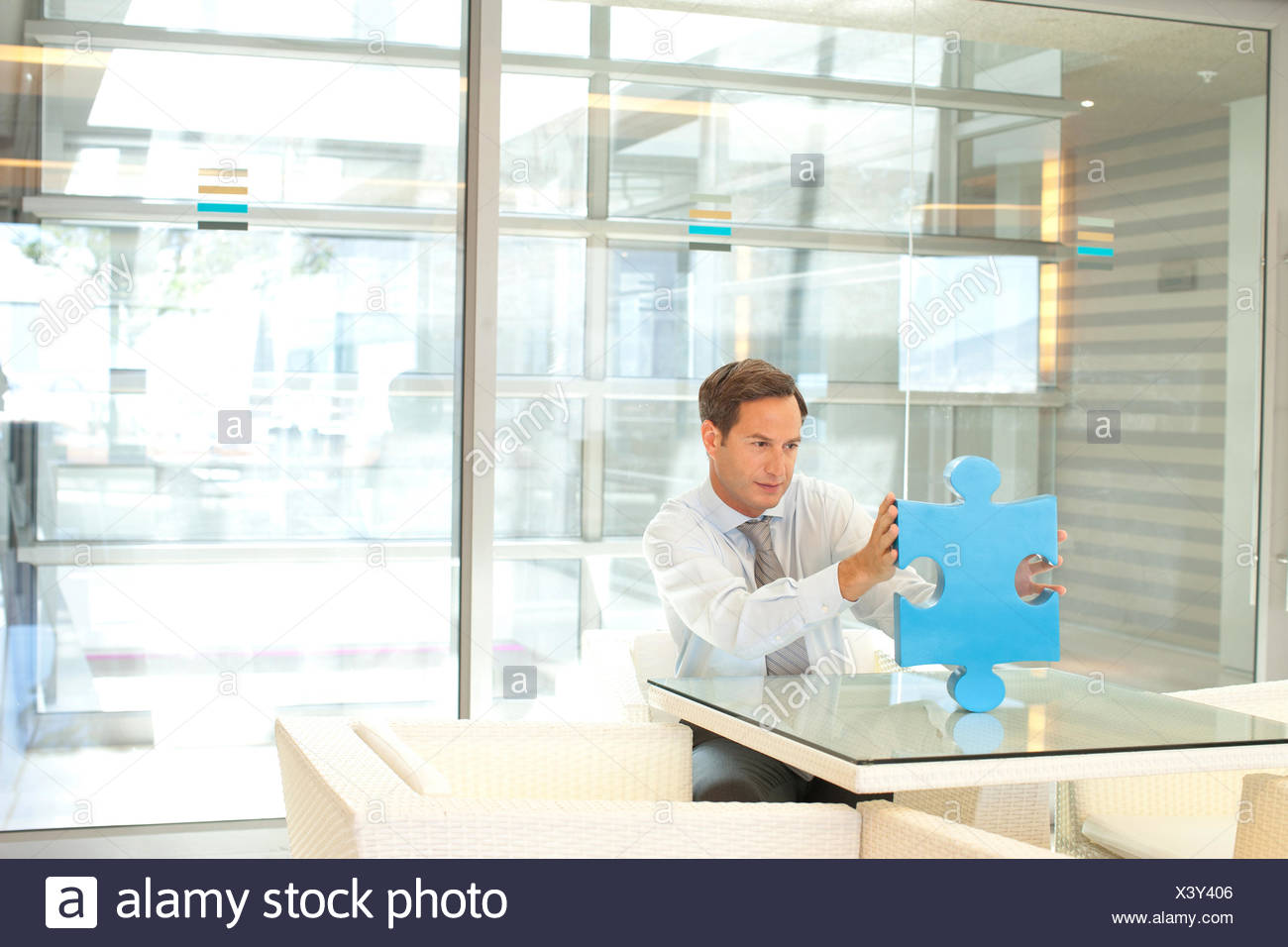 Businessman looking at jigsaw puzzle piece - Stock Image