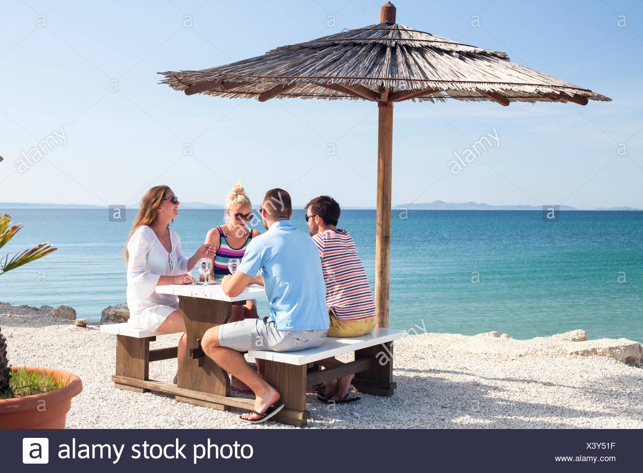 Group of friends sitting at table in beach bar - Stock Image
