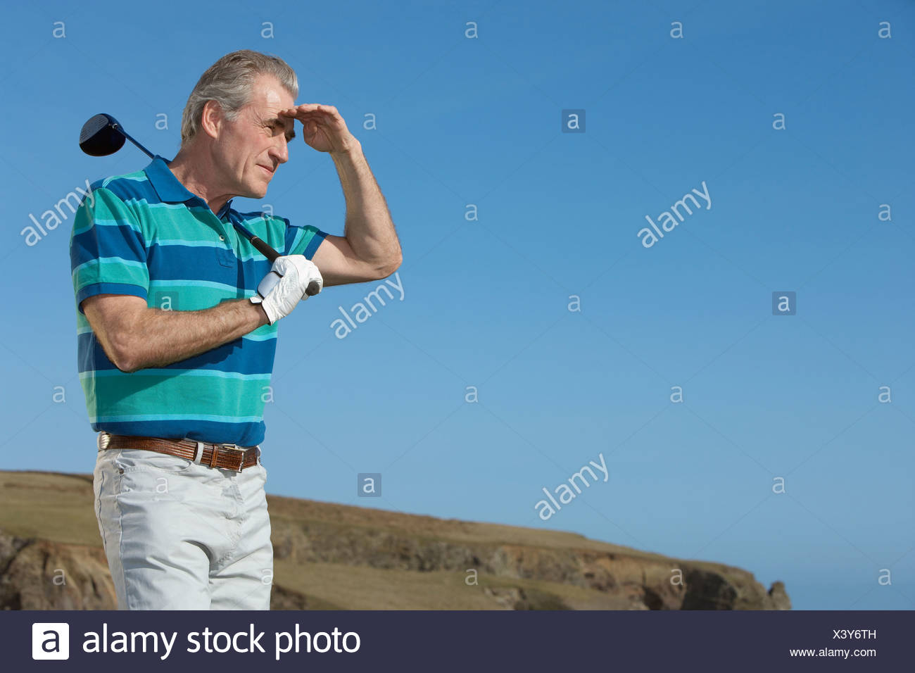 man golfing trying to see where his drive went - Stock Image