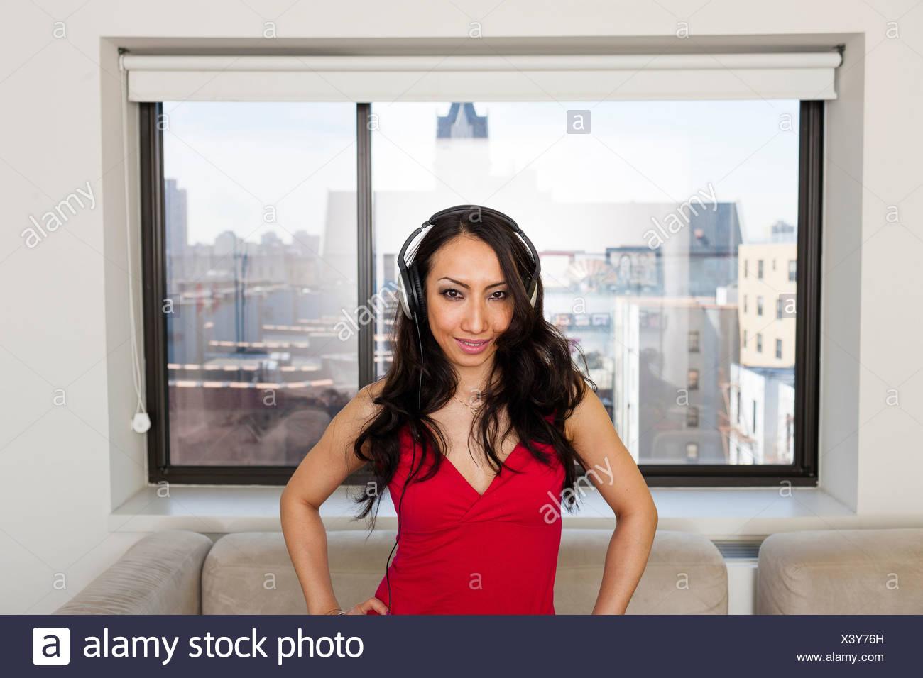Mid adult woman wearing headphones, portrait - Stock Image