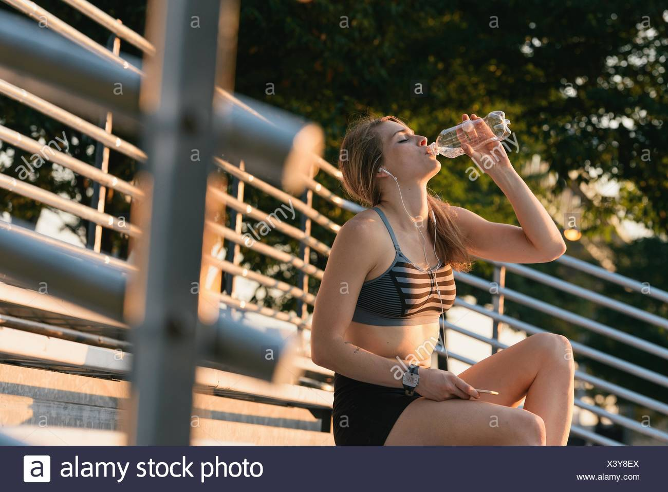 Young woman sitting outdoors, drinking from water bottle - Stock Image