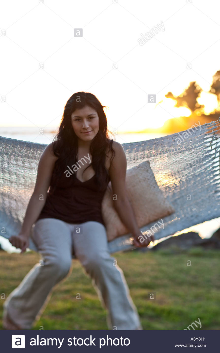 A portrait of a Latino teenage woman sitting in a hammock by the sea at sunset. - Stock Image