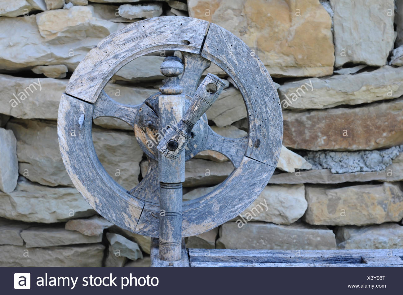 Retro Spinning Wheel Against Stone Wall Background - Stock Image