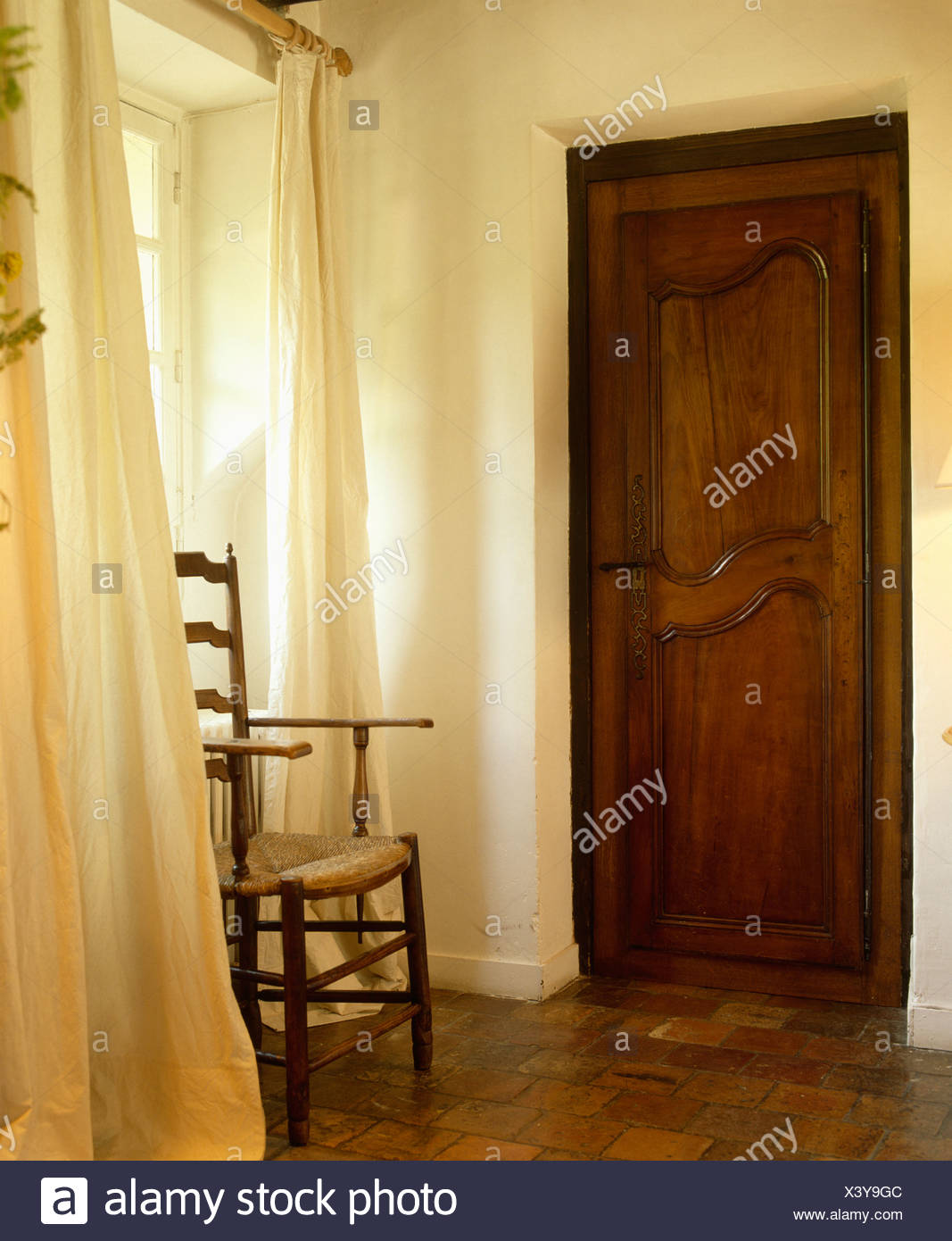 Antique Rush Seated Ladderback Chair In Front Of Window With White Curtains In Small Hall With Carved Wooden Door Stock Photo Alamy