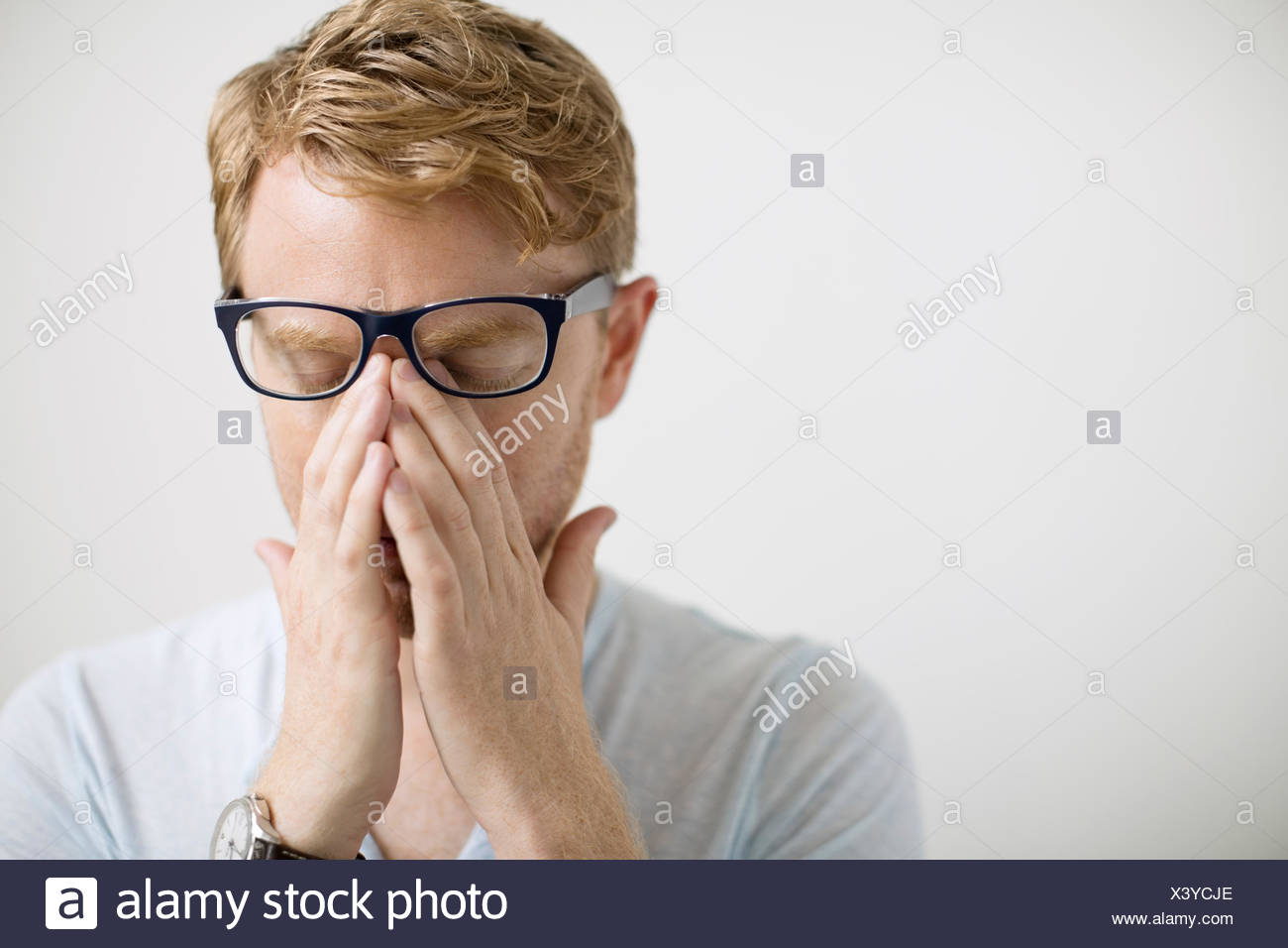 Blonde man rubbing eyes under eyeglasses - Stock Image