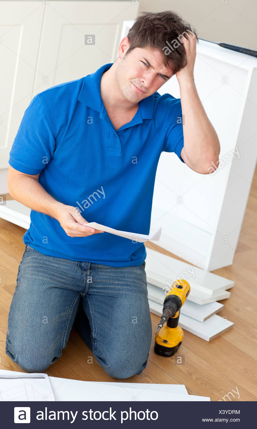 Incomprehensive man reading the instructions to assemble furniture in the kitchen - Stock Image