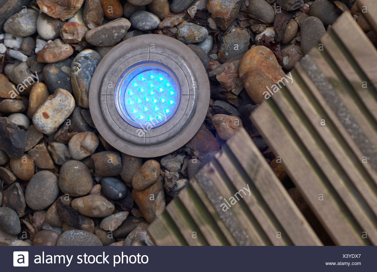 blue LED uplighter recessed into a pebble border - Stock Image