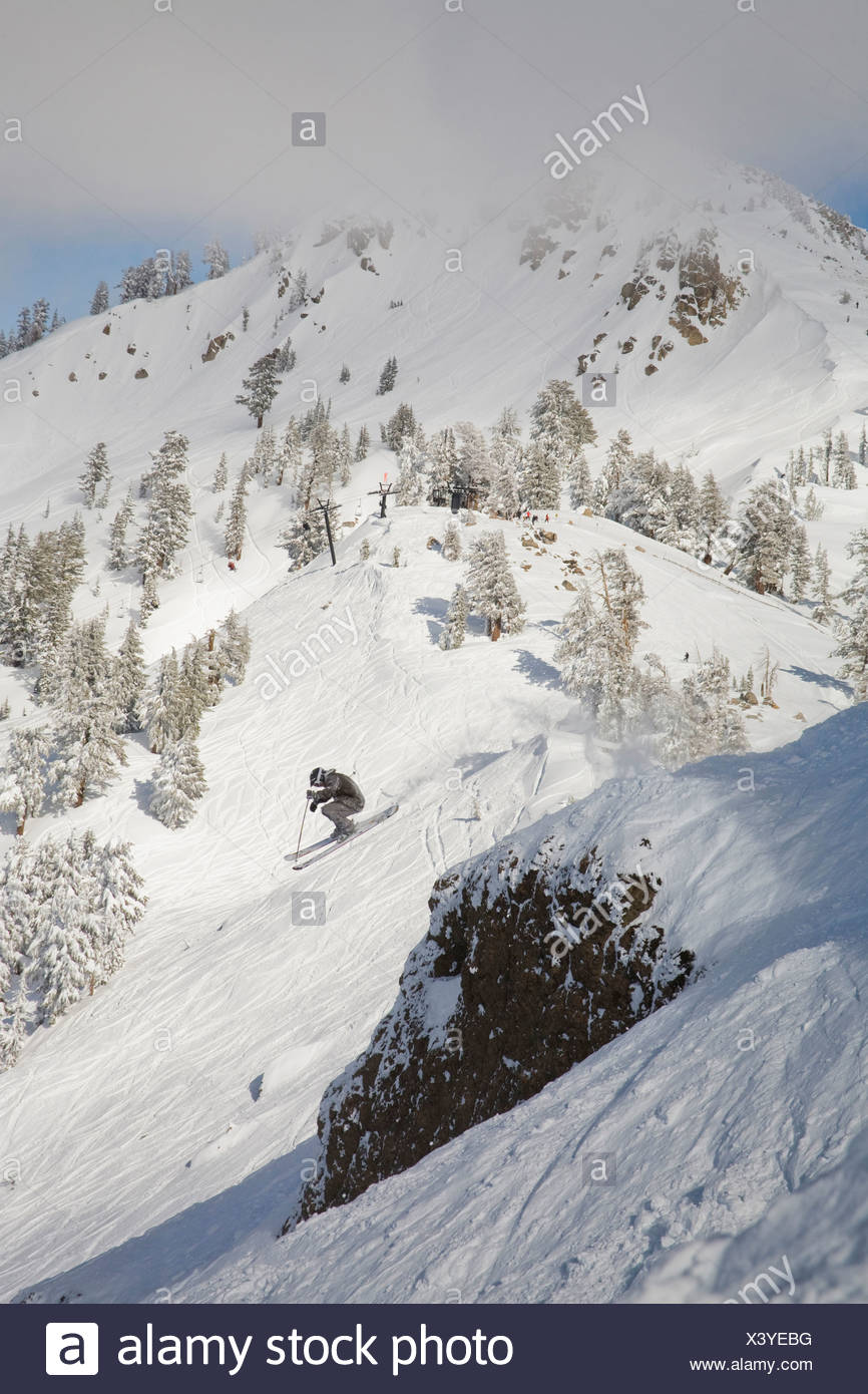 A skier launches off a cliff into fresh powder snow. - Stock Image