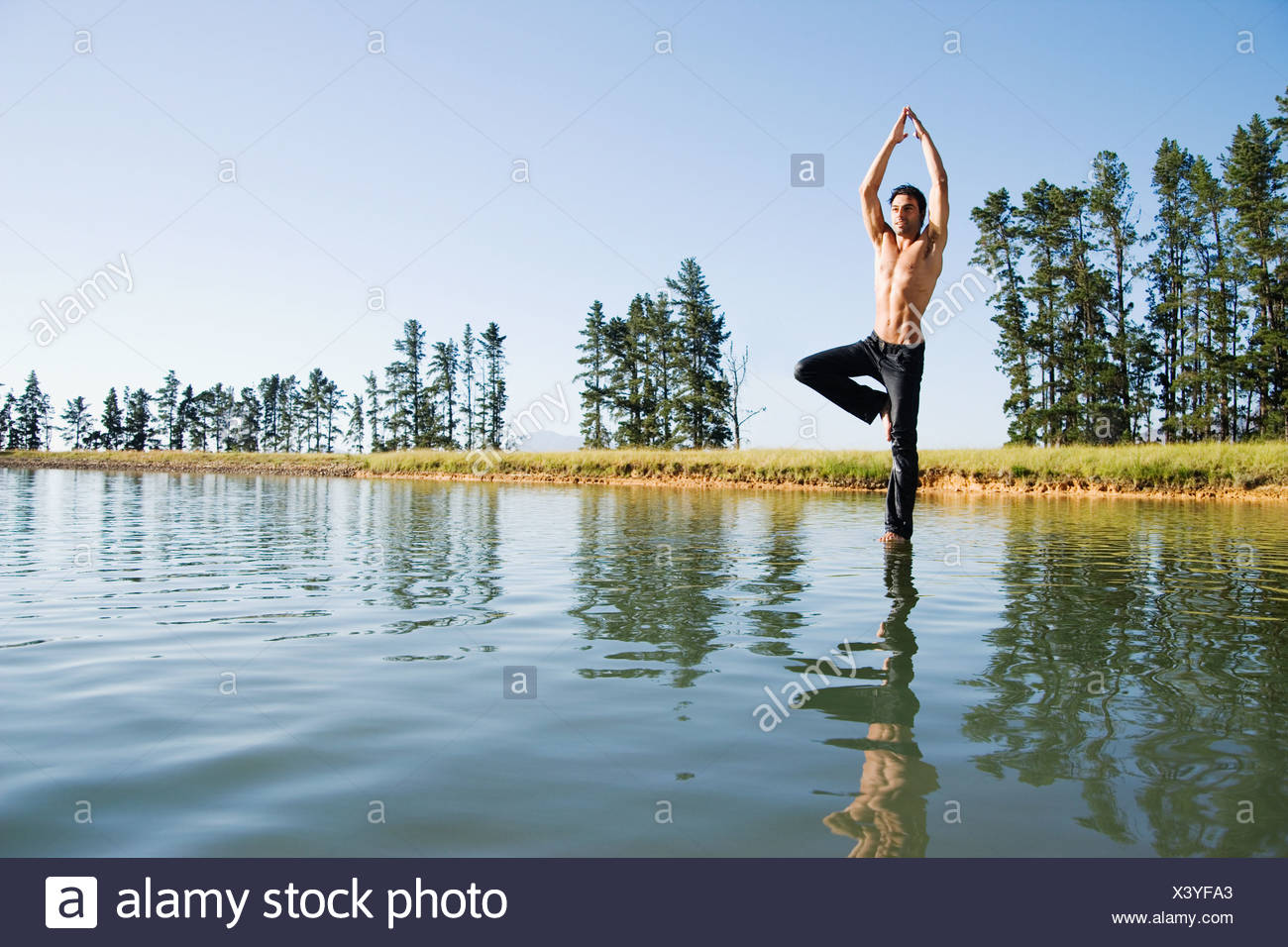 Man doing yoga on water with trees Stock Photo