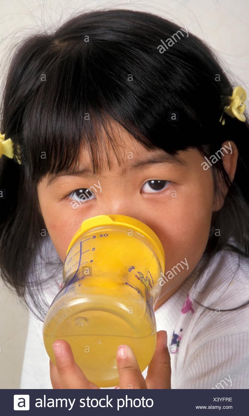 Little Chinese girl drinking orange juice from beaker - Stock Image